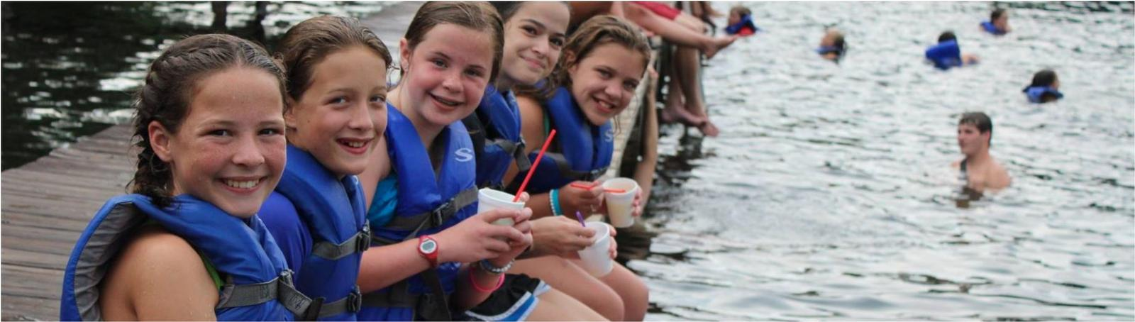 girls in life preservers sitting on a dock